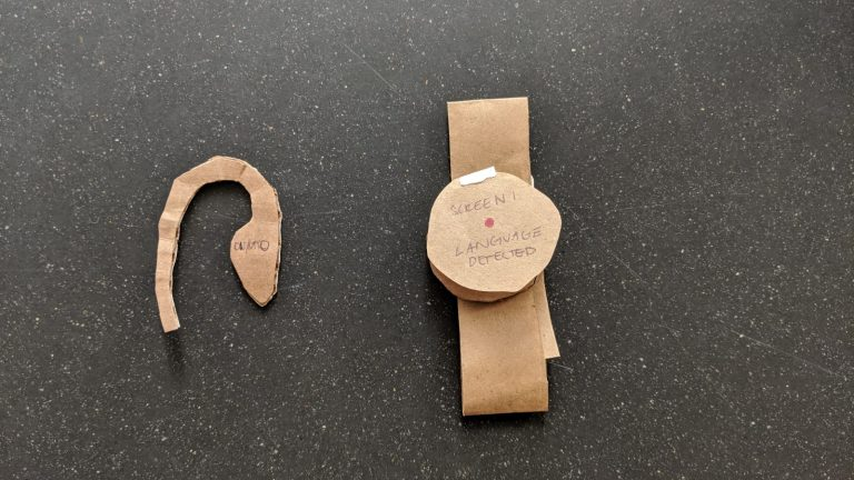 Universal translator watch and headphone prototype in cardboard.
