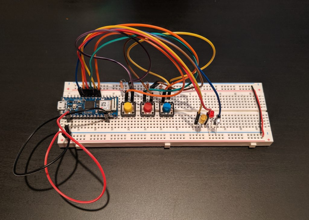 Arduino Nano connected to three buttons and three LED lights on a breadboard with jumper cables.